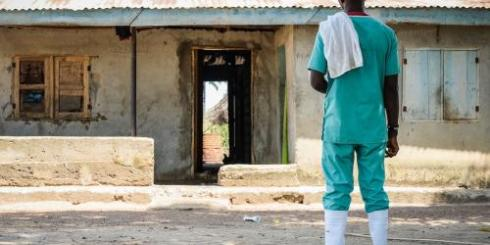 A health worker in front of a clinic.