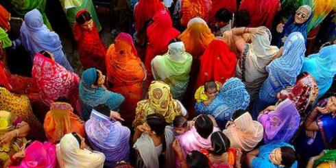 group of people with backs to camera, likely women but some heads are covered, in bright colorful garb