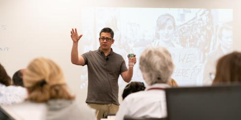 A man speaks to a group in front of a projected image of a woman holding a sign.