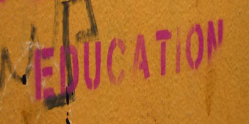 Orange wall with pink block letters that say For a Better Education