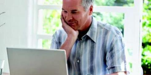middle-aged man sitting at a computer with hand cupping chin, smiling