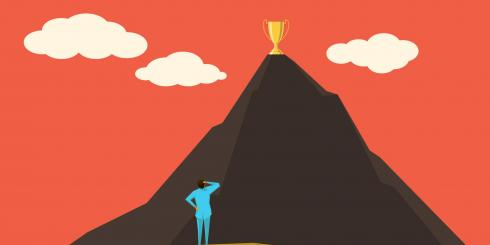 Man standing at foot of mountain with trophy on top of mountain