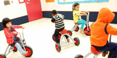 Four kids on trikes riding around the classroom.