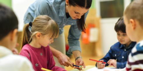 Teacher assisting children on a task in the classroom.