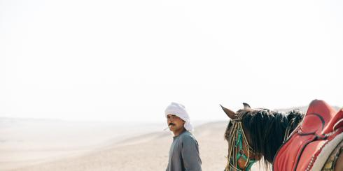 Man walking in the desert with horse.