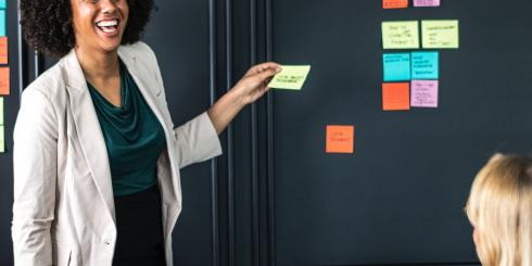 Woman standing in front of wall with post-it notes.