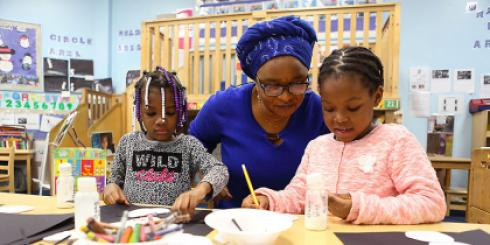 Teacher working with two kids on art project.