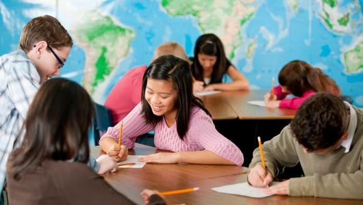 A group of adolescent students in a classroom with a map on the wall in the background.