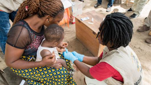 Health worker administering a shot to a child being held by the mother