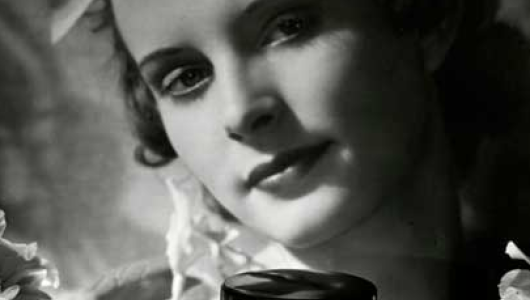 Black and white photographic advertisement showing a woman's face with a jar of skin product in the foreground