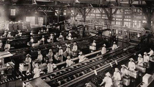 Black and white historical photograph of people working in a factory