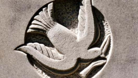 Stone carving showing a dove holding an olive branch in its beak