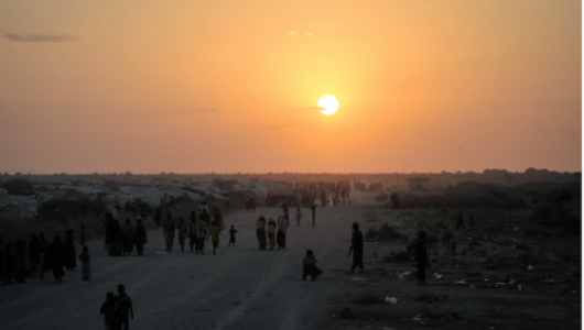 Groups of people in a refugee camp walking beneath an orange sunset sky