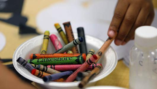 Child reaching for crayons to color.