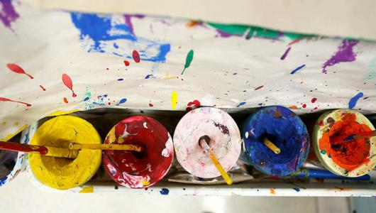 Paint cups by an easle.