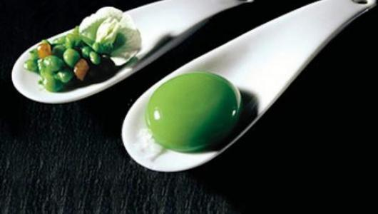 Two spoons, one holding intact peas and a pea flower, the other with a spherification of pea soup.